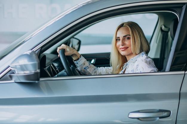 Ältere frau, die ein auto im autohaus testet