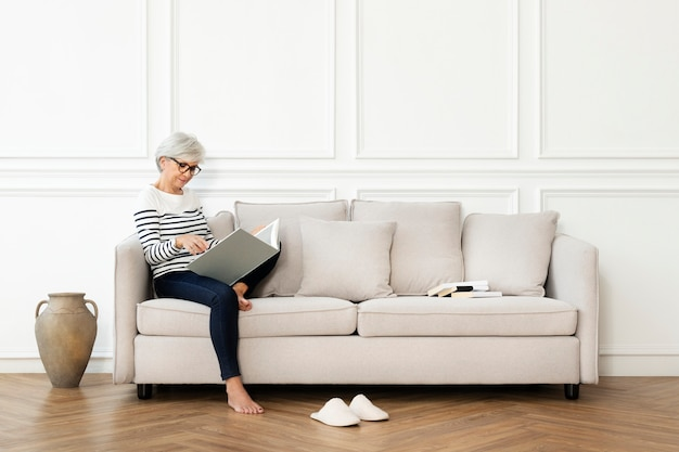 Ältere frau, die ein buch auf dem sofa in einem skandinavischen dekor-wohnzimmer liest