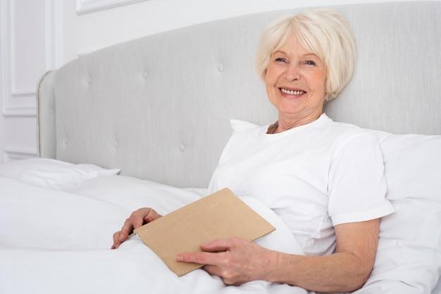 Ältere frau, die ein buch im schlafzimmer hält