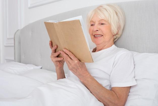 Ältere frau, die ein buch im schlafzimmer liest