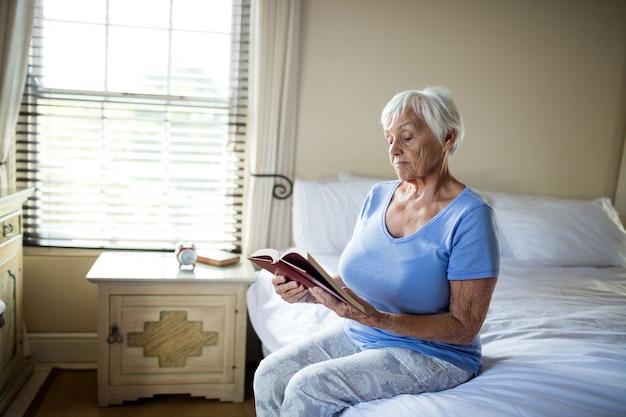 Ältere frau, die ein buch im schlafzimmer zu hause liest