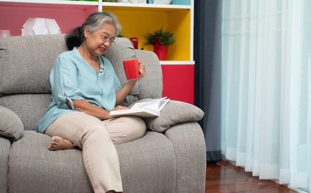 Ältere frau, die ein buch liest, genießen und entspannen, allein zu hause bleiben und den ruhestand genießen