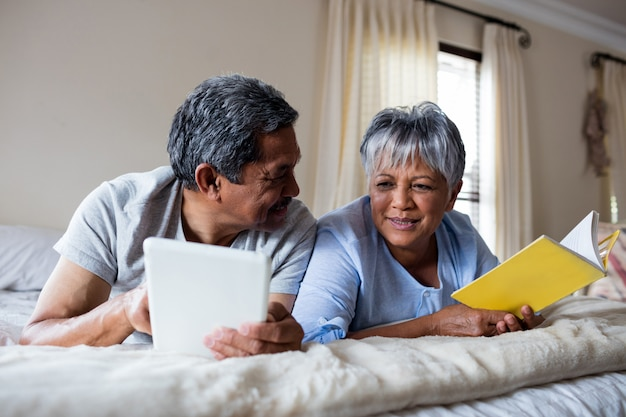 Ältere frau, die ein buch und einen älteren mann liest, die digitale tablette auf bett verwenden