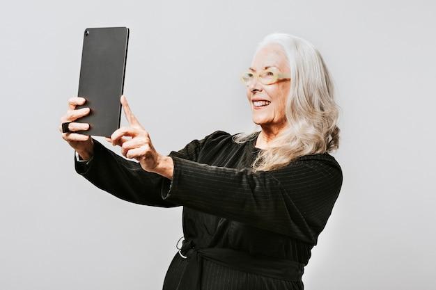 Ältere frau, die ein foto von sich selbst mit einem digitalen tablet macht