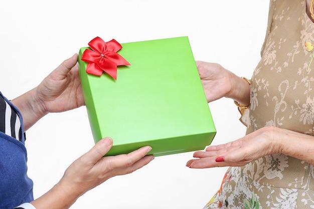 Ältere frau, die ein geschenk von der tochter erhält