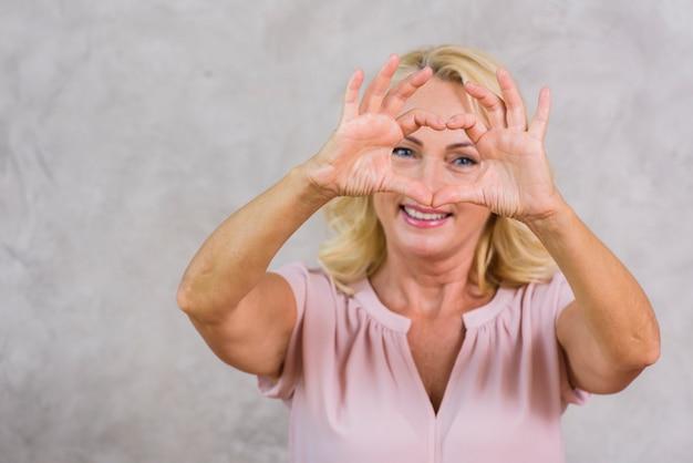 Ältere frau, die ein herz mit ihren fingern macht