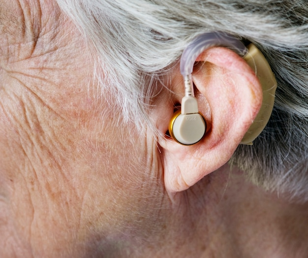 Ältere frau, die ein hörgerät trägt