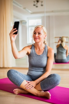 Ältere frau, die ein selfie auf yogamatte nimmt