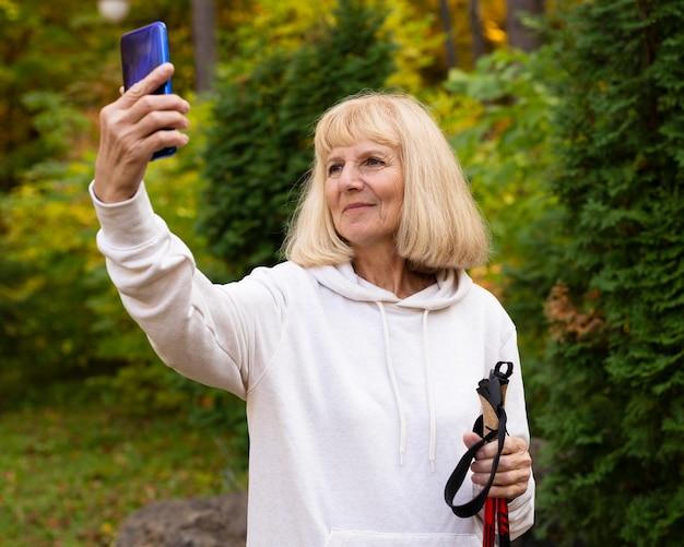 Ältere frau, die ein selfie beim wandern im freien nimmt