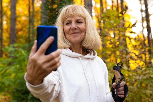 Ältere frau, die ein selfie beim wandern in der natur nimmt