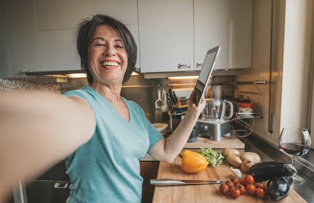 Ältere frau, die ein selfie kochendes gemüse nimmt