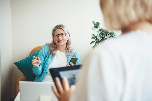 Ältere frau, die ein treffen zu hause hat, während sie einen laptop benutzt und eine brille trägt