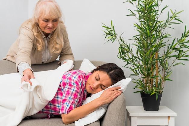 Ältere frau, die eine decke auf ihre erschöpfte tochter schlafend auf das sofa setzt
