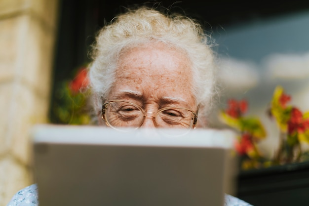 Ältere frau, die eine digitale tablette verwendet