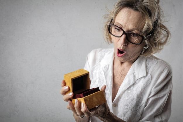 Ältere frau, die eine geschenkbox öffnet