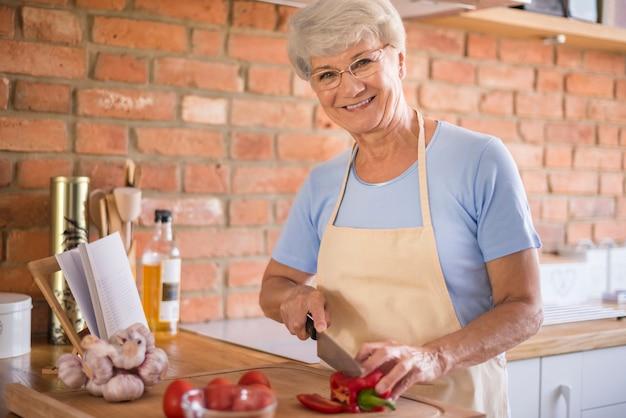 Ältere frau, die eine mahlzeit vorbereitet