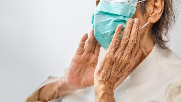 Ältere frau, die eine maske trägt, um vor coronavirus covid-19 zu schützen