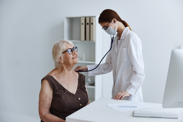 Ältere frau, die eine medizinische maske am arztstethoskop trägt. foto in hoher qualität