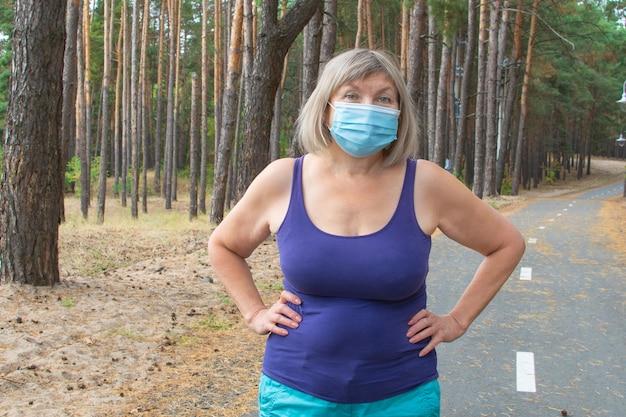 Ältere frau, die eine medizinische maske trägt, die draußen im park läuft