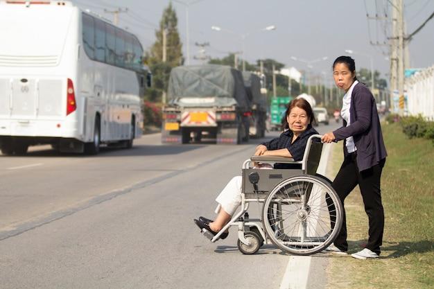 Ältere frau, die eine rollstuhlkreuzstraße benutzt