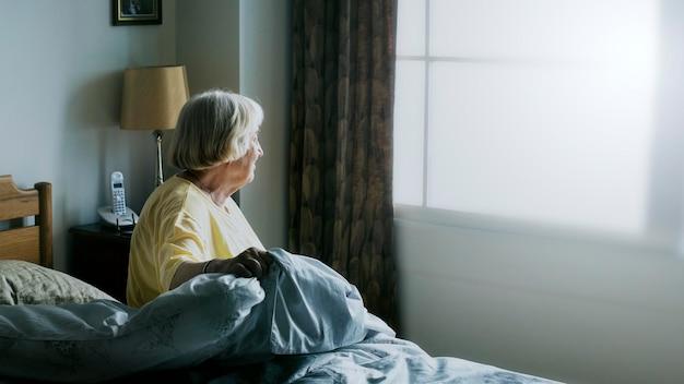 Ältere frau, die eine selbstisolation in einem schlafzimmer hat