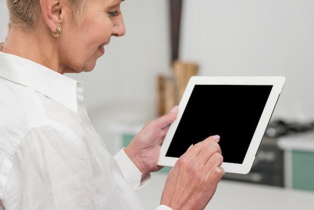 Ältere frau, die eine tablettennahaufnahme hält