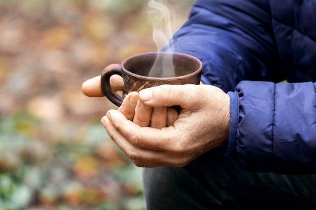 Ältere frau, die eine tasse heißen tee im wald in der natur hält. erholung im freien