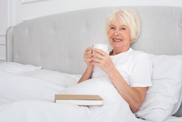 Ältere frau, die eine tasse im schlafzimmer liest