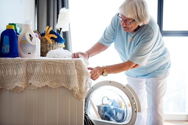 Ältere frau, die eine wäscherei tut