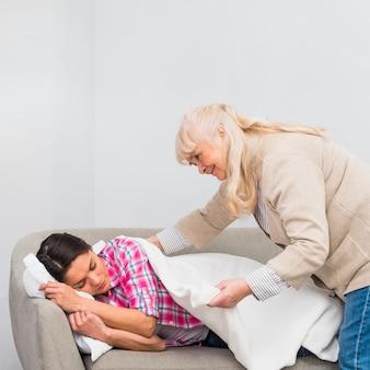 Ältere frau, die eine weiße decke auf ihre tochter schläft auf dem sofa setzt