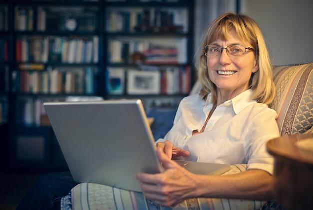 Ältere frau, die einen laptop verwendet