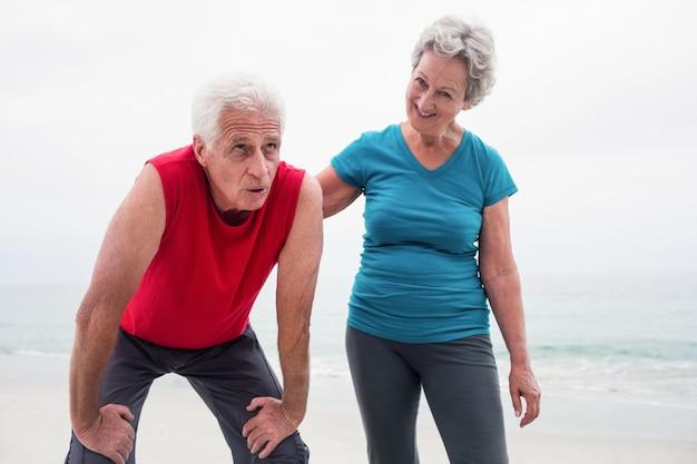 Ältere frau, die einen müden älteren mann tröstet