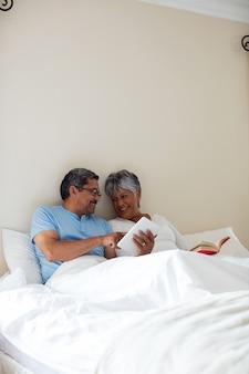 Ältere frau, die einen roman und einen älteren mann liest, der digitales tablett auf bett verwendet