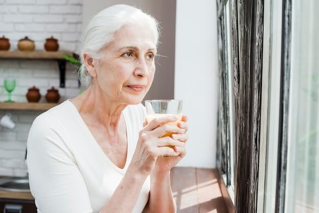Ältere frau, die einen saft isst