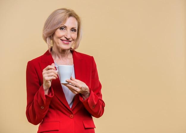 Ältere frau, die einen tasse kaffee mit kopienraum hält