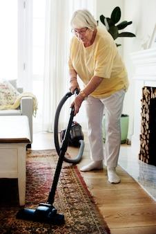 Ältere frau, die einen teppich saugt