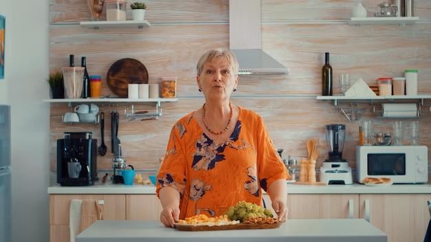 Ältere frau, die einen videoanruf in der küche hat, während seine familie das abendessen im hintergrund zubereitet. pov online-internet-moderne konferenz, chatten, kommunikation, chat-gespräch über webc