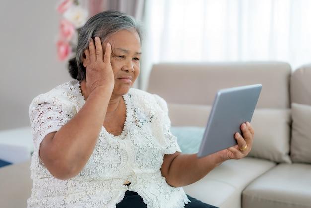 Ältere frau, die einen videoanruf mit ihrem arzt mit ihren kopfschmerzen auf digitaler tablet-online-gesundheitsberatung für digitale technologie macht, während sie zu hause bleibt.