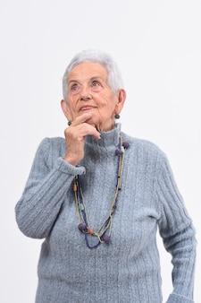 Ältere frau, die einen zweifel oder eine frage über weißen hintergrund hat