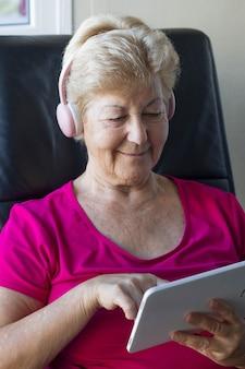 Ältere frau, die elektronische geräte zur ablenkung und information manipuliert
