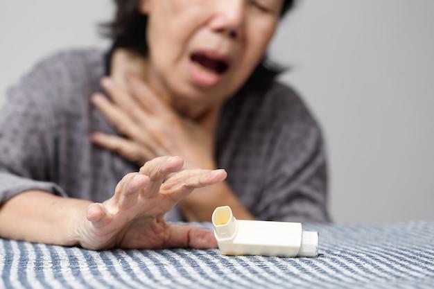 Ältere frau, die erstickt und ein asthmaspray hält