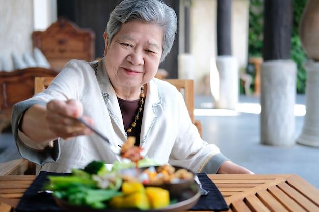 Ältere frau, die essen isst