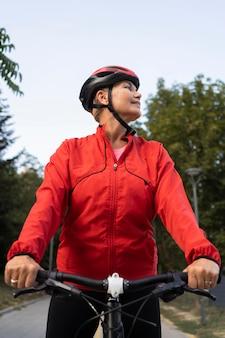 Ältere frau, die fahrrad draußen reitet