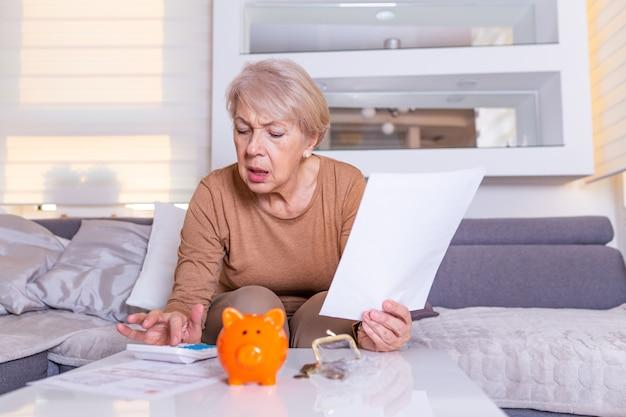 Ältere frau, die finanzen zu hause tut. ältere frau mit taschenrechner und euro-geld zu hause zählen. business-, spar-, rentenversicherungs-, alters- und personenkonzept