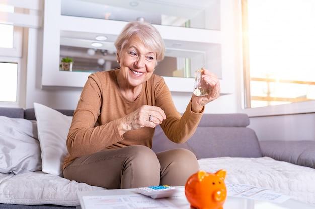 Ältere frau, die finanzen zu hause tut. glückliche ältere frau mit taschenrechner und euro-geld zu hause zählen. business-, spar-, rentenversicherungs-, alters- und personenkonzept