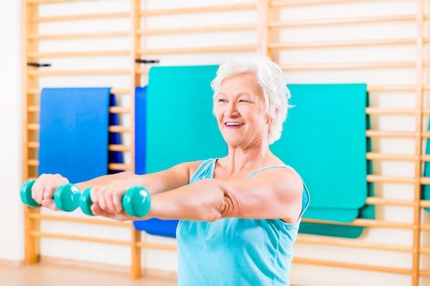 Ältere frau, die fitness-sport im fitnessstudio mit hanteln tut