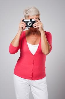 Ältere frau, die foto durch retro-kamera nimmt