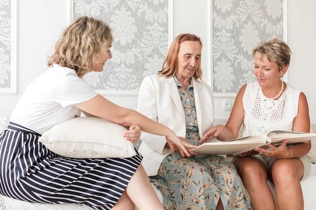 Ältere frau, die fotoalbum mit ihrer tochter und großartigen tochter schaut