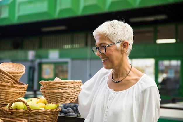 Ältere frau, die frisches organisches gemüse auf markt kauft