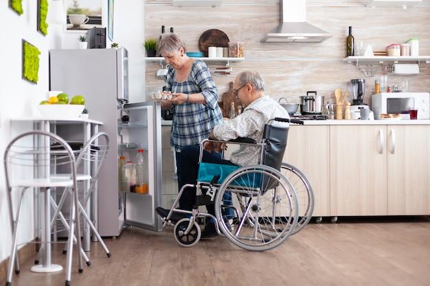 Ältere frau, die frühstück für behinderten ehemann zubereitet, der eierkarton aus dem kühlschrank nimmt und mit einem mann mit gehbehinderung lebt. behinderter älterer mann im rollstuhl, der seiner frau in der küche hilft